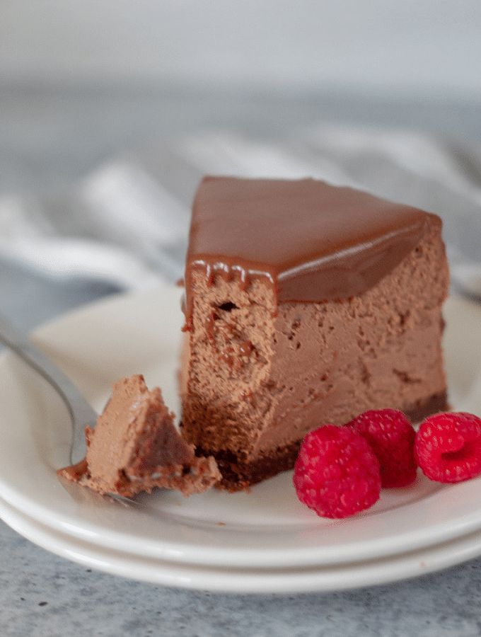 a single slice of keto chocolate cheesecake on a white plate with raspberries on the side.