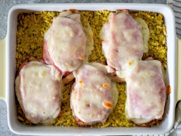 Keto baked chicken over cauliflower rice pilaf in a yellow casserole dish