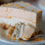 a single slice of keto orange creamsicle cheesecake on a white plate topped with fresh orange zest