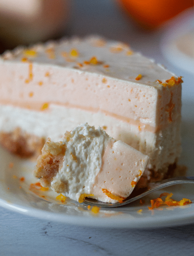 A single slice of keto orange creamsicle cheesecake on a white plate topped with freshly grated orange zest