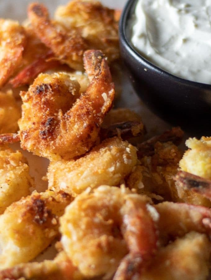 golden and crispy keto coconut shrimp on a white plate with a bowl of pina colada dipping sauce on the side