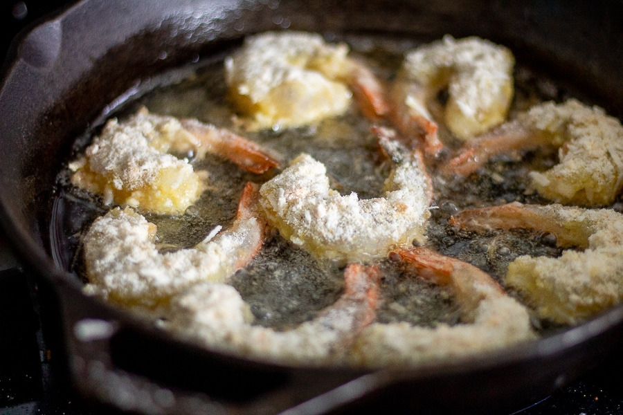 low carb coconut shrimp frying in a cast iron skillet