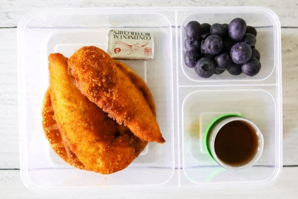 Chicken. waffles, butter, syrup, and blueberries in a lunch box.