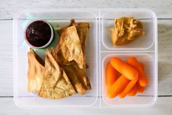Peanut butter, jelly, carrots, and low carb pita crisps in a lunch box.