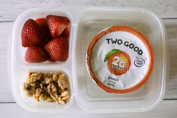 a kids lunch with peach two good yogurt, strawberries, and walnuts
