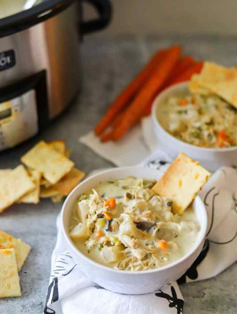 A bowl of creamy chicken pot pie soup with crackers and a slow cooker in the background