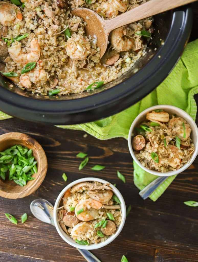 low carb jambalaya in a crockpot with green onions and two white bowls of jambalaya on the side