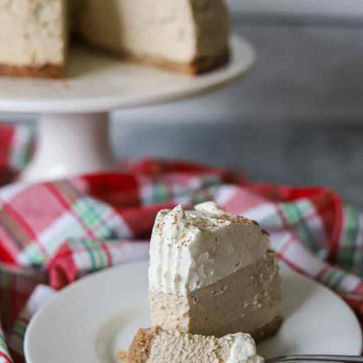 A slice of keto eggnog cheesecake on a white plate with one bite taken.