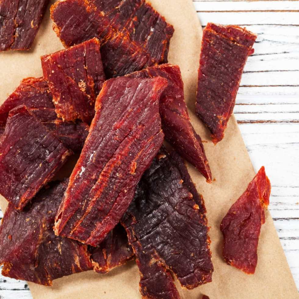 Beef jerky strips on a wooden cutting board