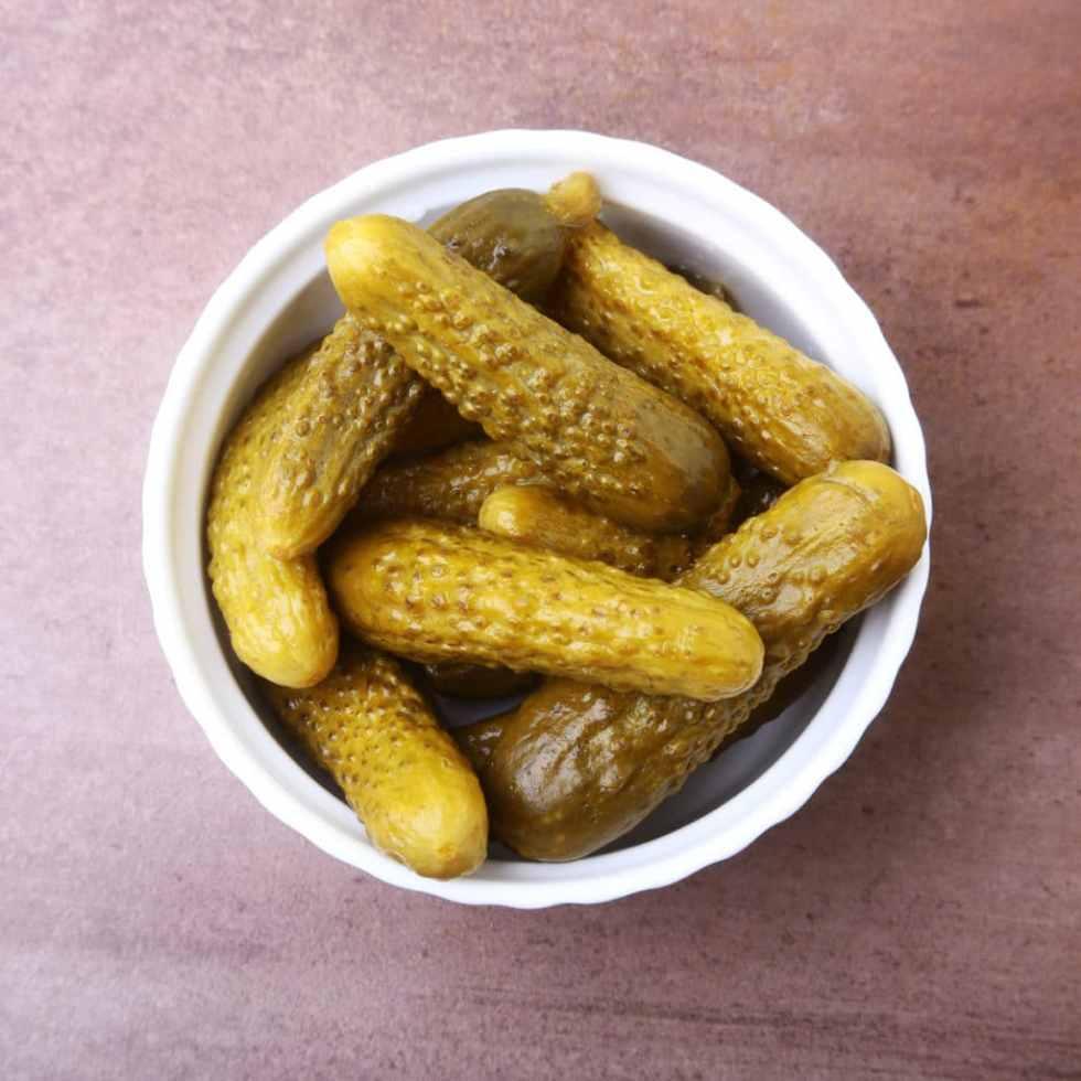 a white ramekin full of pickles