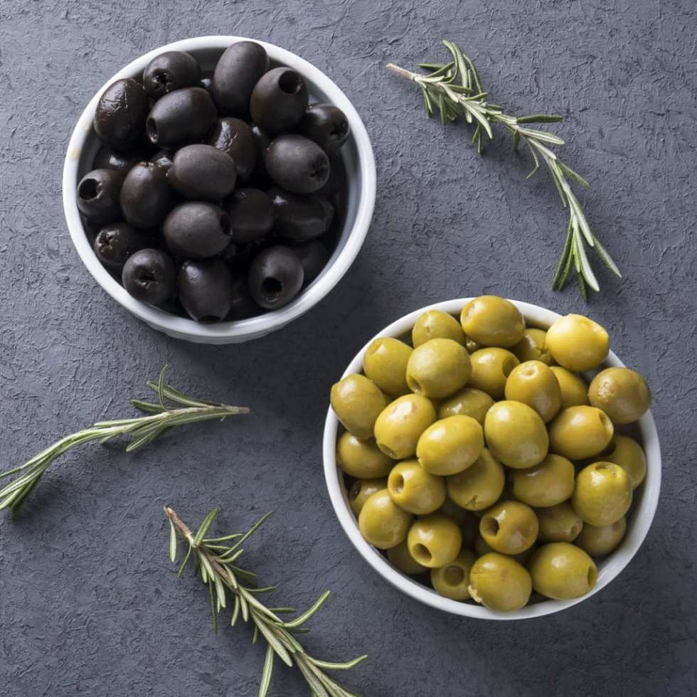 two white bowls of olives, one with green olives and the other with black olives. Rosemary sprigs are off to the side.