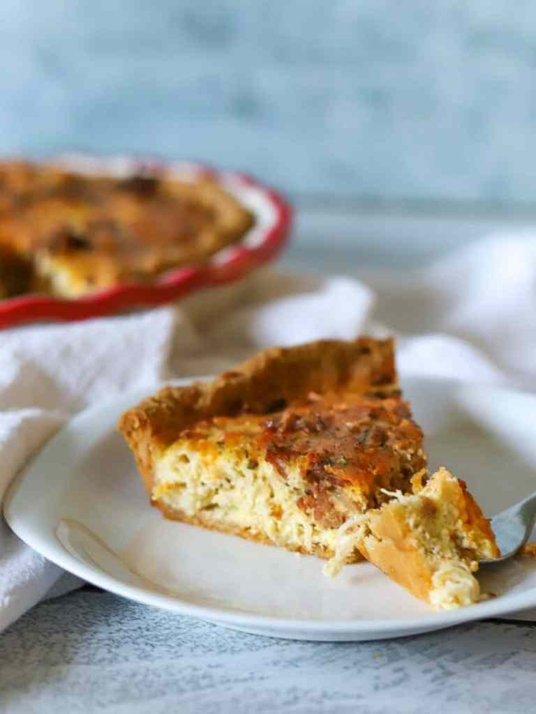 A single slice of crack chicken quiche on a white plate with one bite taken