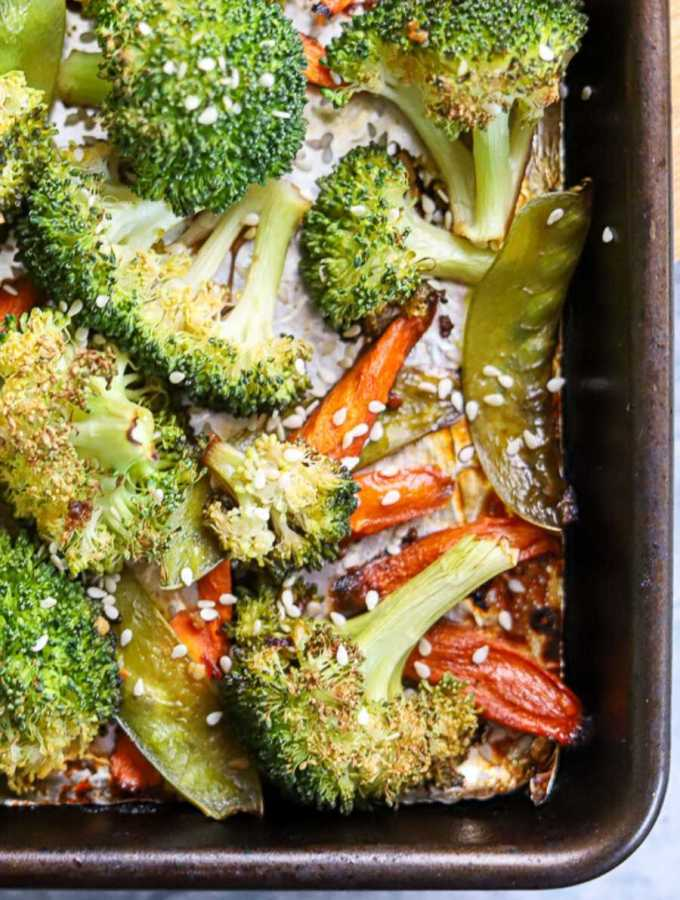 a sheet pan with roasted broccoli, carrots, and snow peas topped with sesame seeds