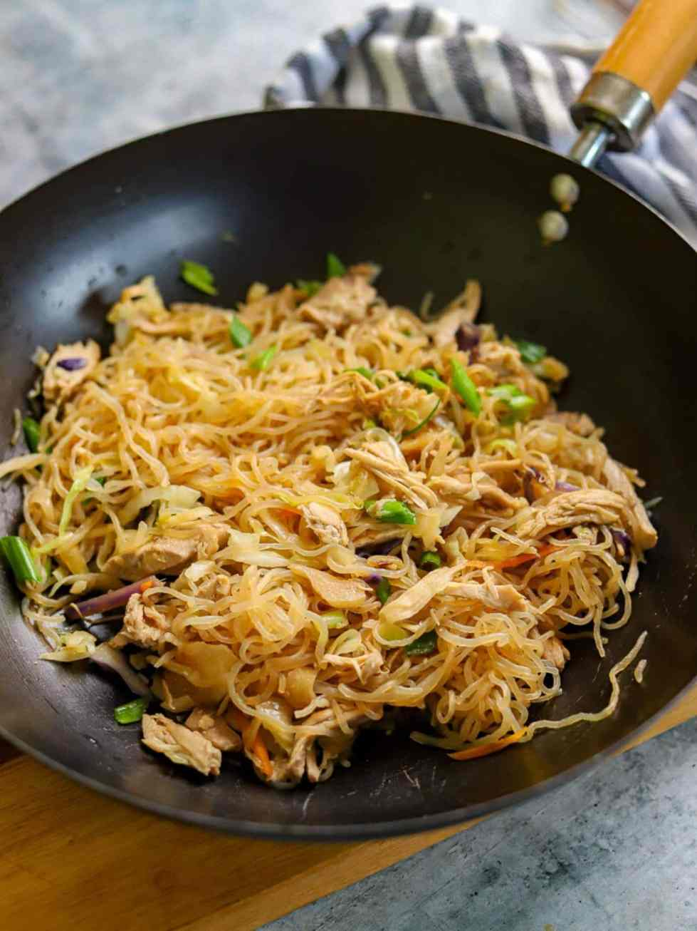 Asian noodles and vegetables cooked together in a wok