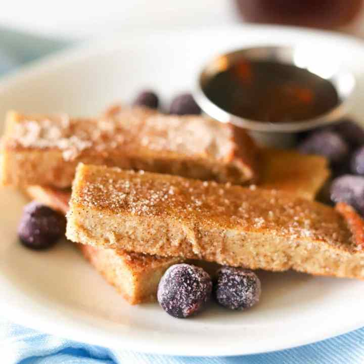 a plate full of homemade french toast sticks with blueberries and a silver cup of sugar free maple syrup.
