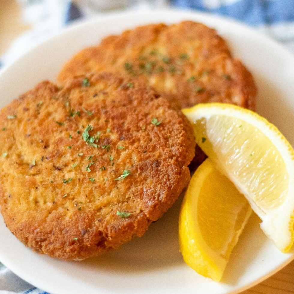 two salmon patties on a white plate garnished with lemon wedges and parsley