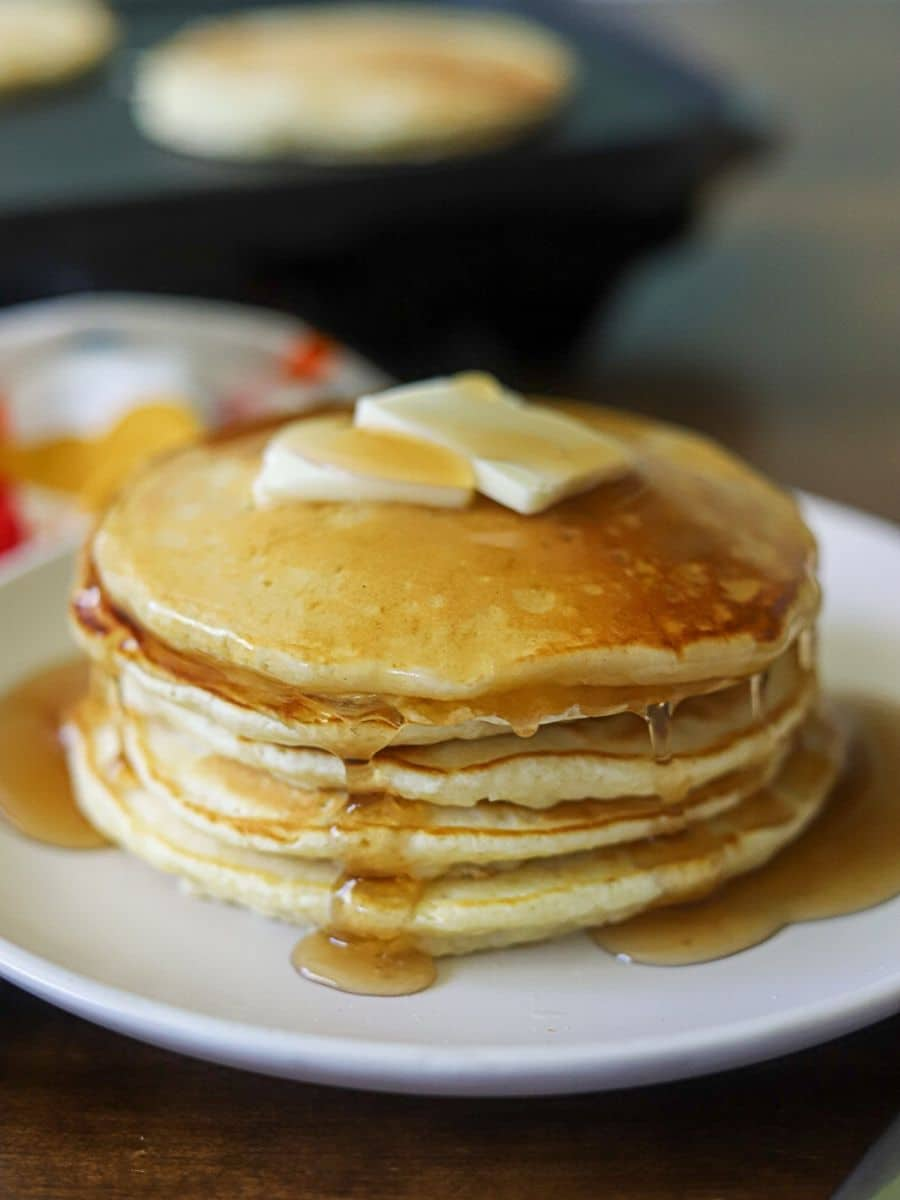 A stack of pancakes on a white plate, topped with two pats of butter and maple syrup.