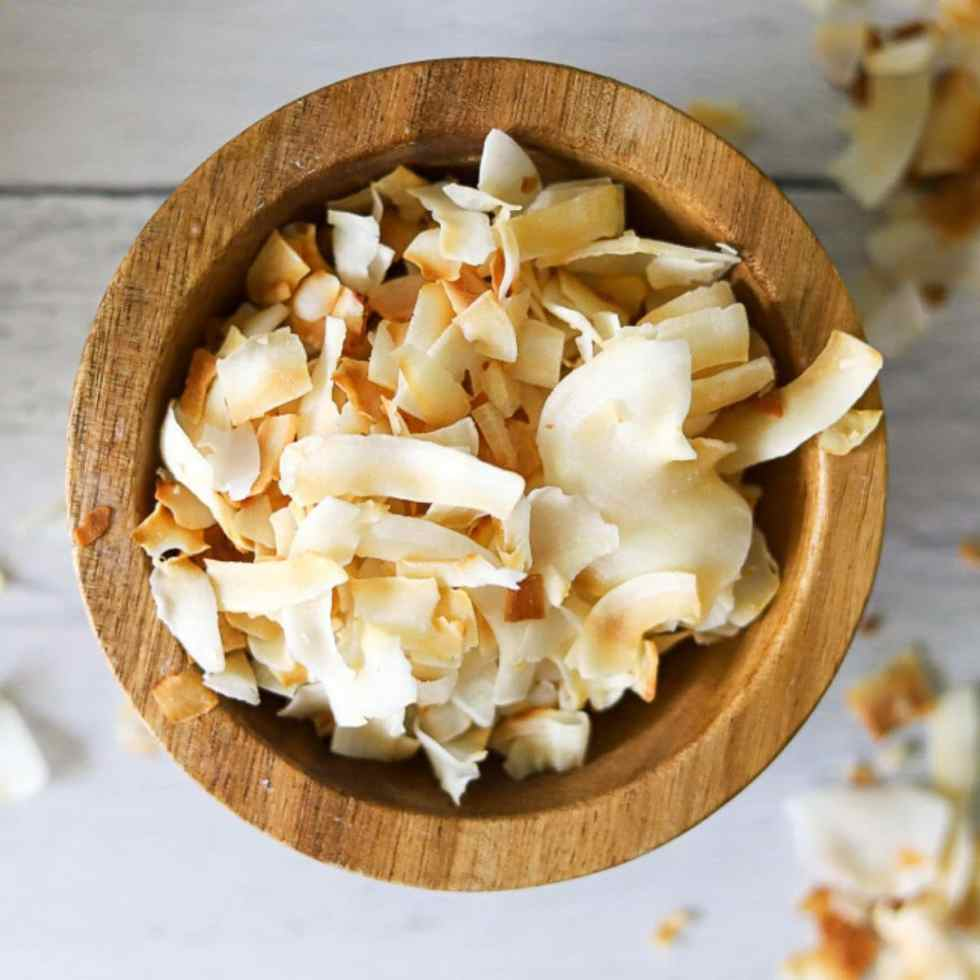 a wooden bowl of toasted coconut flakes.