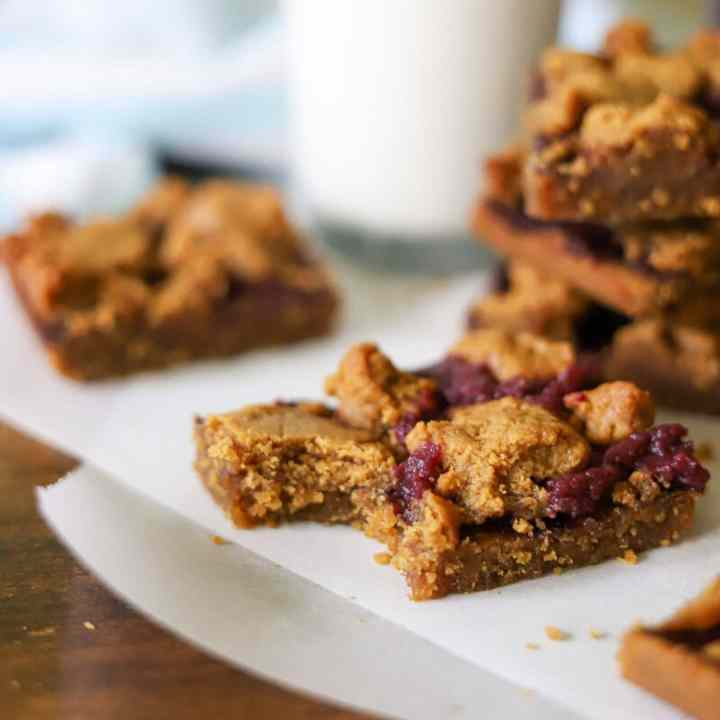 peanut butter and jelly bars on a piece of parchment paper. One has a bite taken and a glass of milk is in the background.