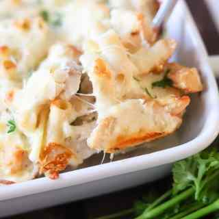 A close up image of chicken alfredo casserole being scooped out of a casserole dish.
