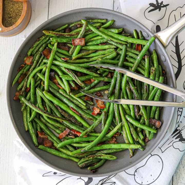 sautéed green beans in a skillet with crisp bacon and garlic.