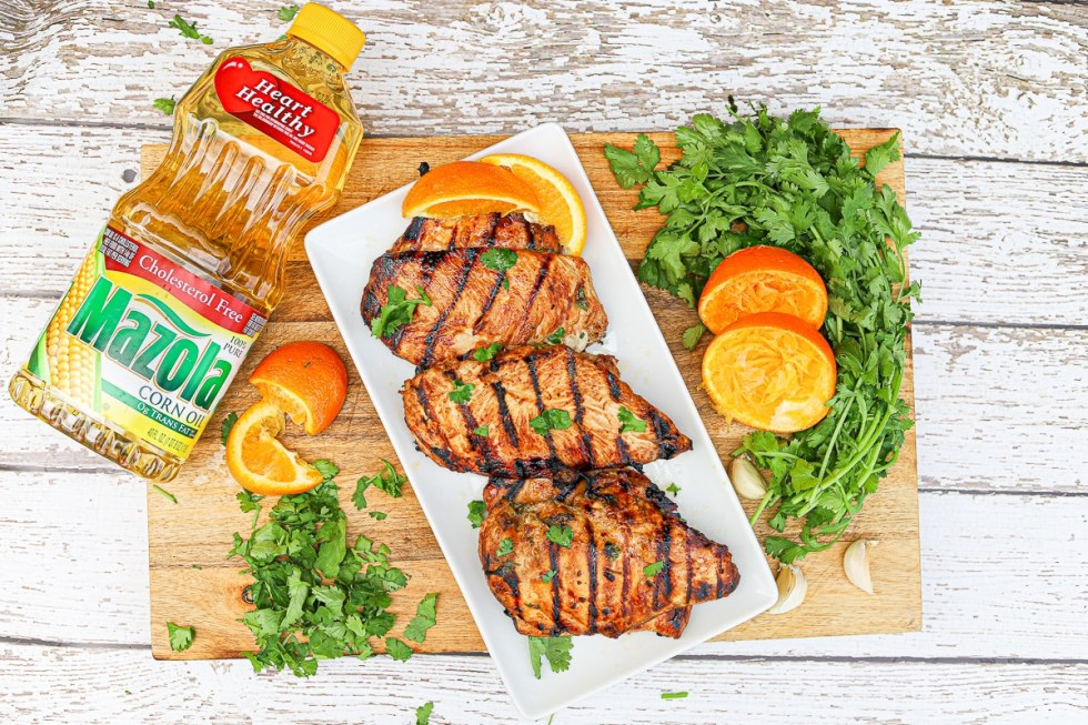 a wooden cutting board with a white platter full of grilled chicken with cilantro, oranges, and a bottle of oil off to the side