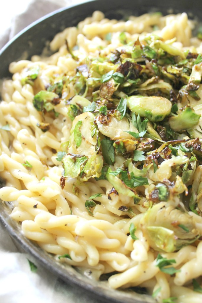 This Creamy Vegan Garlic Pasta with Crispy Brussels Sprouts is simple to make and the perfect Fall dinner to keep you warm and satisfied! | ThisSavoryVegan.com #vegan #veganpasta