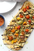 This Vegan Eggplant & Hummus Flatbread combines thin slices of eggplant, creamy hummus and balsamic cherry tomatoes & garlic. A great snack to share or a dinner to eat on your own   ThisSavoryVegan.com #vegan #veganpizza