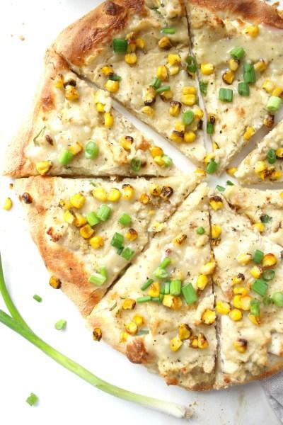 This Vegan Mashed Potato White Pizza is the ultimate comfort food. Creamy white base, mashed potatoes, fresh corn and savory gravy on top of crispy crust   ThisSavoryVegan.com #vegan #veganpizza