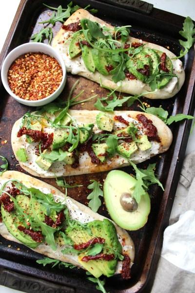 A new take on traditional avocado toast - thesesVegan Cream Cheese Avocado Flatbreads are layered with cream cheese, sun-dried tomatoes, avocado slices and arugula | ThisSavoryVegan.com #vegan #avocadotoast