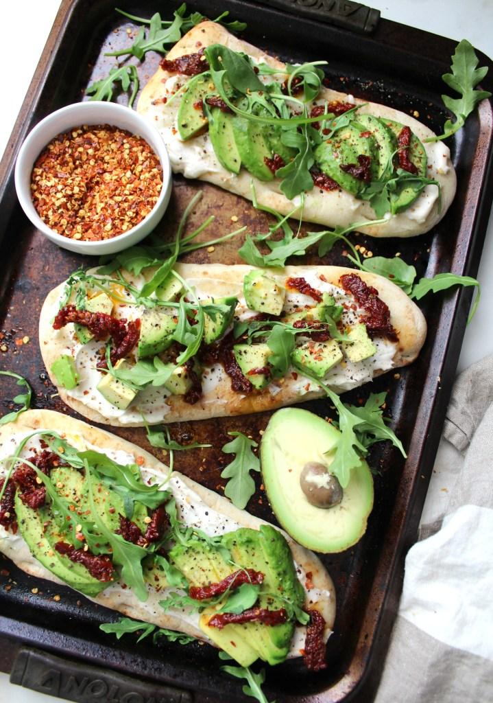 A new take on traditional avocado toast - theseVegan Cream Cheese Avocado Flatbreads are layered with cream cheese, sun-dried tomatoes, avocado slices and arugula | ThisSavoryVegan.com #vegan #avocadotoast