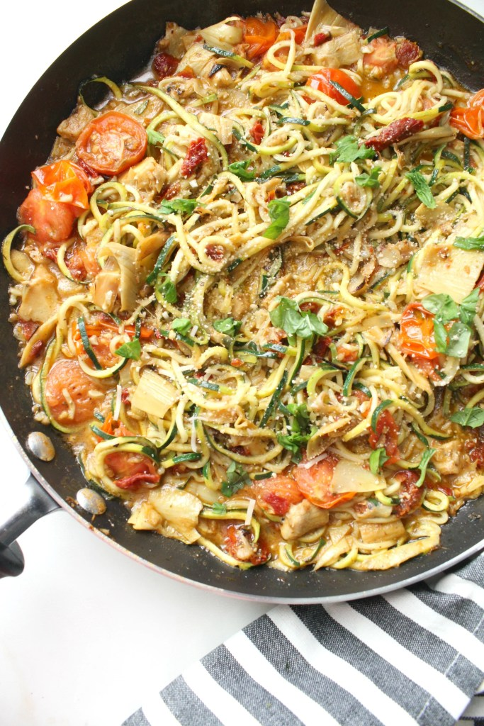 """Lighten up """"pasta night"""" with theseMediterranean Zucchini Noodles. A simple dinner recipe that combines cherry tomatoes, sun-dried tomatoes & artichoke hearts   ThisSavoryVegan.com #zoodles #veganpasta"""