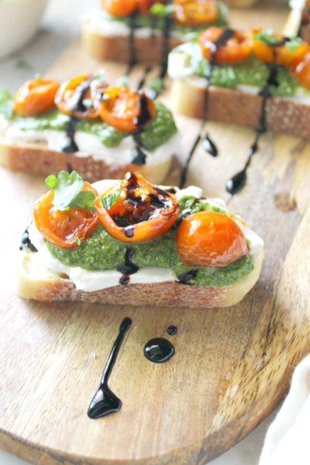These Vegan Cream Cheese Pesto Crostini are the perfect party appetizer. Smooth cream cheese, vibrant pesto and blistered garlicky tomatoes combine to make the perfect topping for crispy bread   ThisSavoryVegan.com #thissavoryvegan #summer #veganappetizer