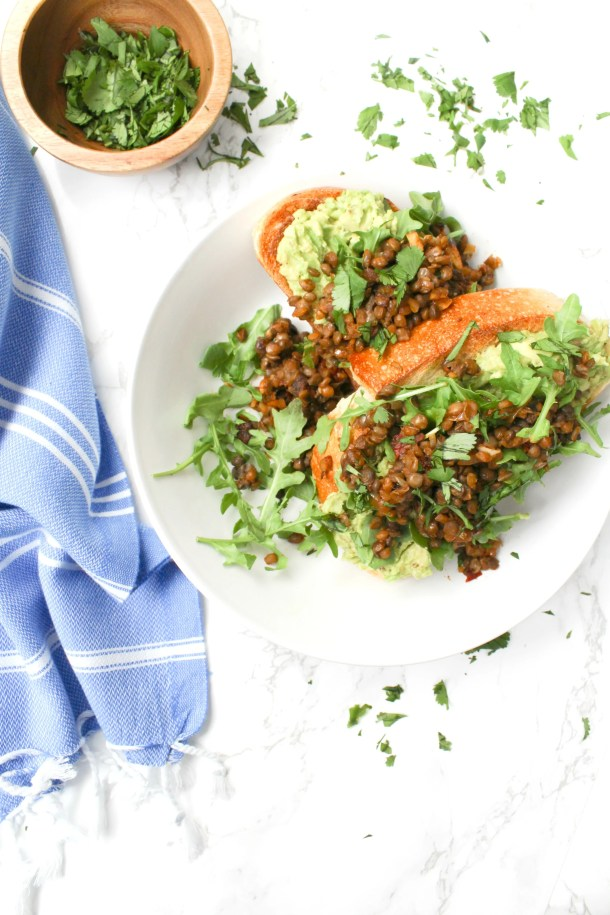 This Chipotle Lentil Avocado Toast is the ultimate vegan brunch meal - sourdough bread topped with avocado, greens and warm chipotle lentils   ThisSavoryVegan.com #thissavoryvegan #vegan #veganbrunch
