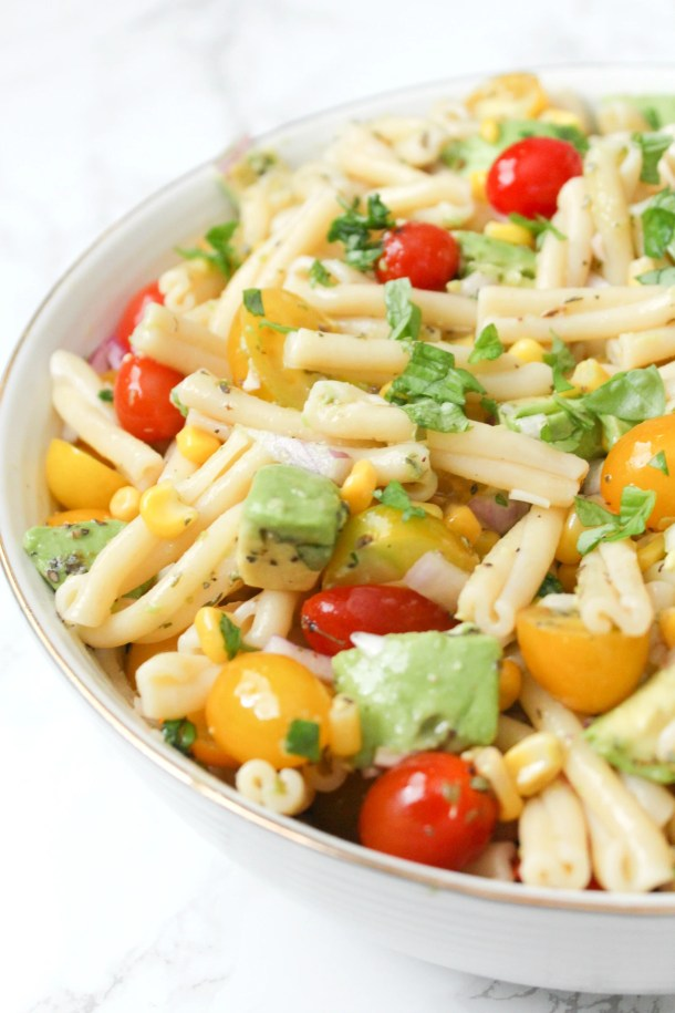 This Tomato Corn Avocado Pasta Salad is filled with fresh ingredients and topped with a light and zesty dressing. Perfect party side dish | ThisSavoryVegan.com #thissavoryvegan #vegan #partyfood