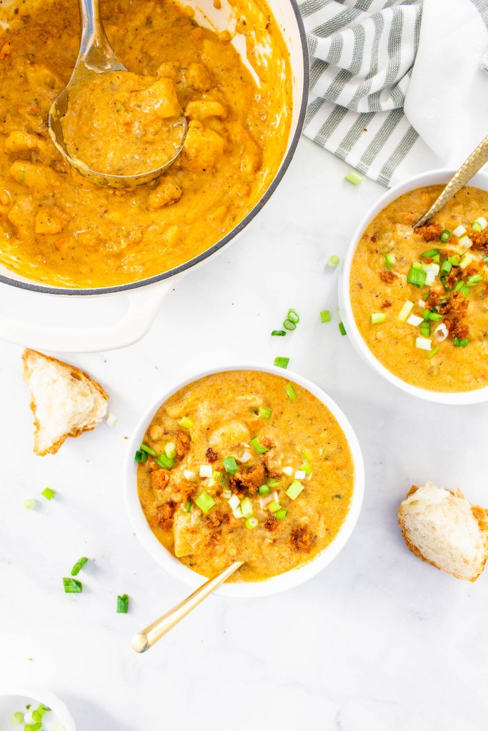 This Vegan Sausage & Potato Beer Cheese Soup is creamy comfort in a bowl. A hearty vegan soup that can be served with crusty bread and green onion | ThisSavoryVegan.com #thissavoryvegan #beercheesesoup #vegansoup