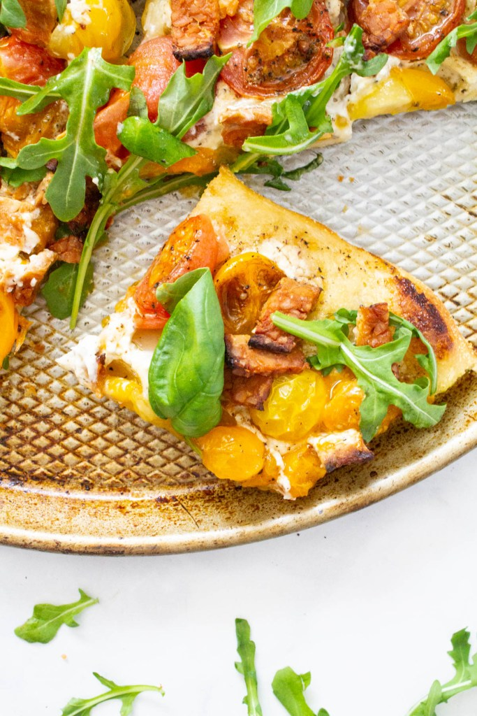 This Vegan BLT Pizza is layered with a rosemary cream sauce, heirloom cherry tomatoes, tempeh bacon and arugula. A fun twist on a classic   ThisSavoryVegan.com #thissavoryvegan #veganpizza #blt