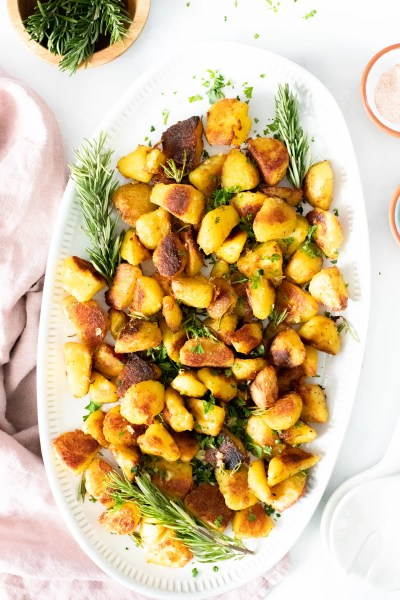 These Crispy Roasted Herb Potatoes are the ultimate vegan potato recipe! Loaded with garlic, rosemary and infused oil | ThisSavoryVegan.com #thissavoryvegan #crispypotatoes #herbpotatoes