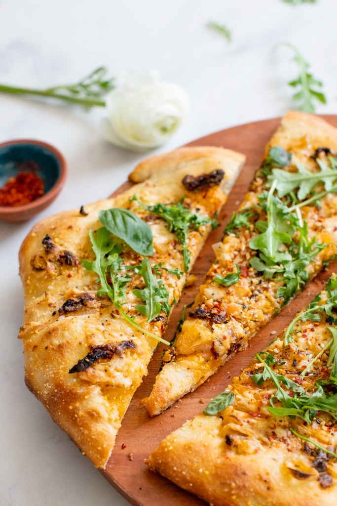 This Everything But the Bagel Vegan Flatbread is made with sun-dried tomatoes, shallots and a white sauce. Topped off with arugula & basil   ThisSavoryVegan.com