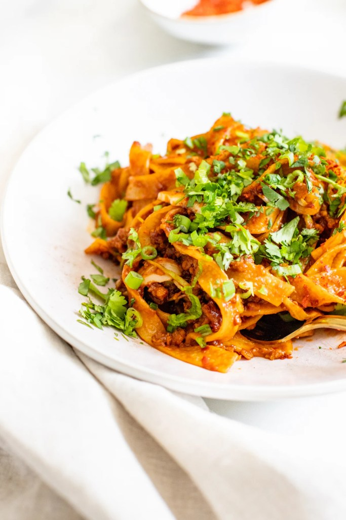 This Spicy Garlic & Ginger Pasta is where East meets West. Vegan beef crumbles are cooked with soy sauce, tomato paste, garlic & ginger | ThisSavoryVegan.com #thissavoryvegan #veganpasta #spicypasta