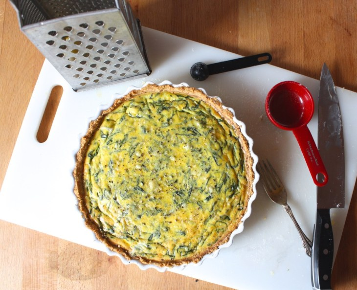 cooked gluten free spinach quiche on counter with cooking utensils and cheese grater