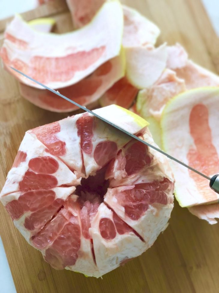a pomelo being peeled with a knife