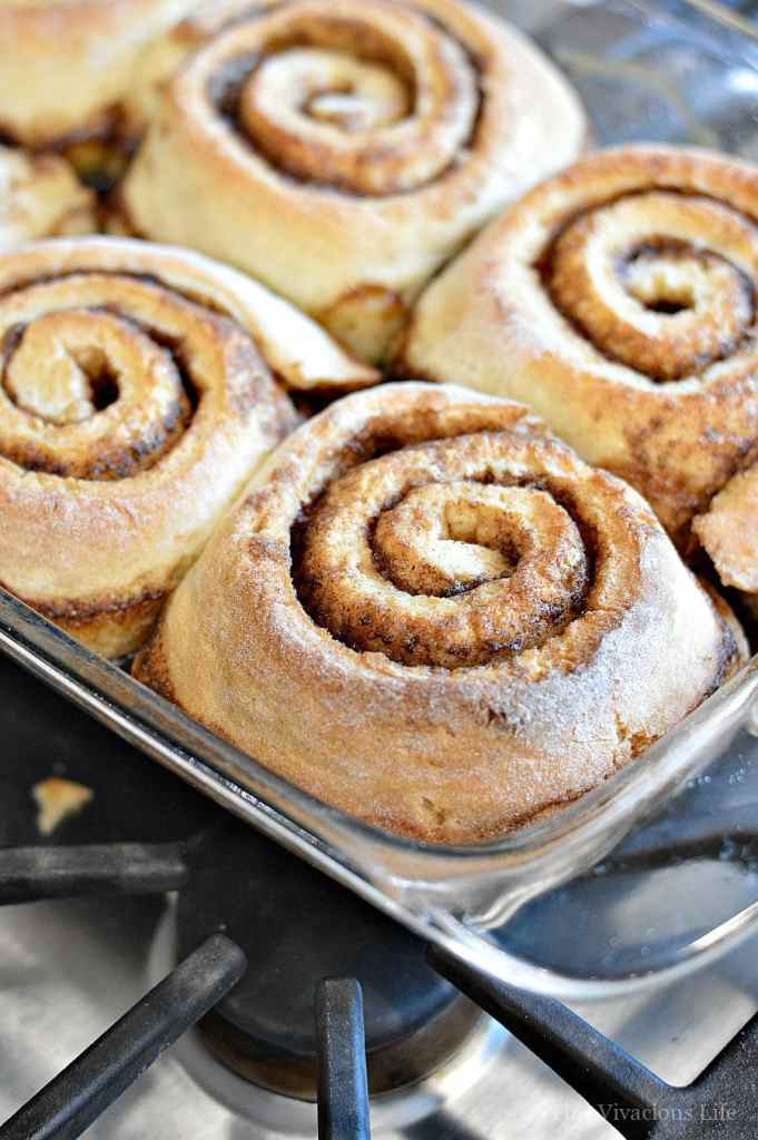 Up close shot of an unfrosted gluten-free cinnamon roll in a glass dish.