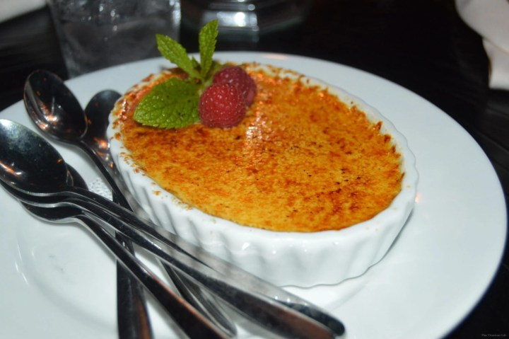 Creme brûlée with raspberries and mint leaves in a white dish