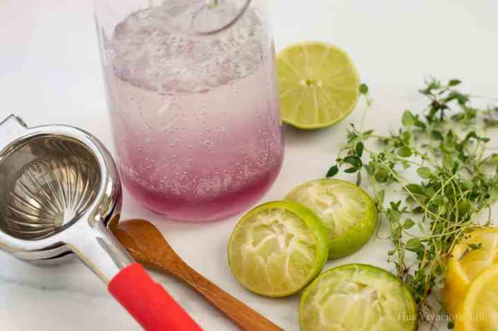 Slices of limes next to a glass pitcher with lavender limeade