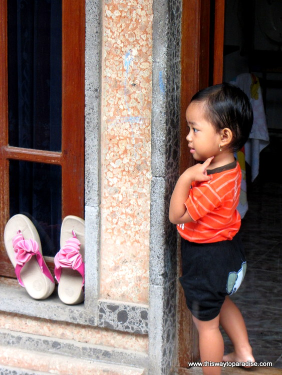 Child at Bali Ceremony peeking around doorway