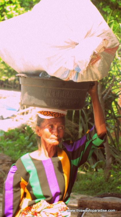 Old woman with goods on head on Gili Air, Gili Islands