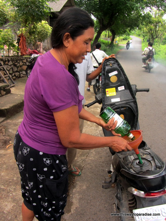 Woman filling motorcycle with petrol in Bali