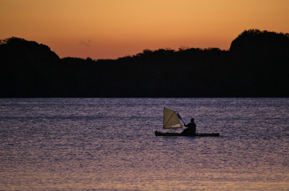 A small watercraft moves through the water at dawn in Cape Hillsborough, Australia