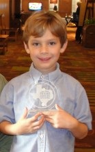 A young boy smiling and holding an award plaque